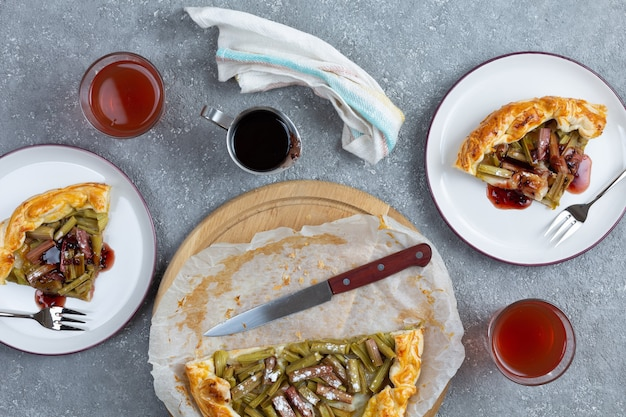Верхний вид открытых пирогов с ревенем на тарелках на сером фоне