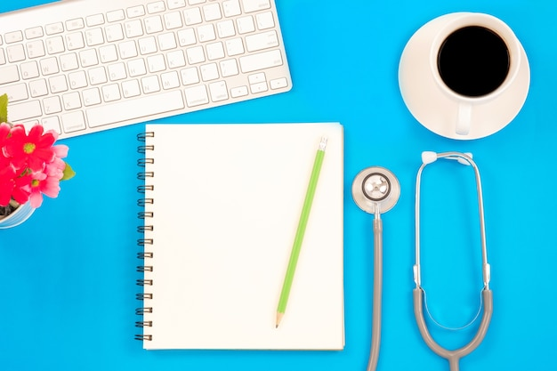 Top viwe of modern workplace with stethoscope and keyboard on blue table background.