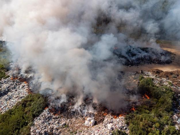 공기를 오염시키는 많은 두꺼운 연기를 내뿜는 쓰레기장에서 쓰레기를 태우는 하향식 보기