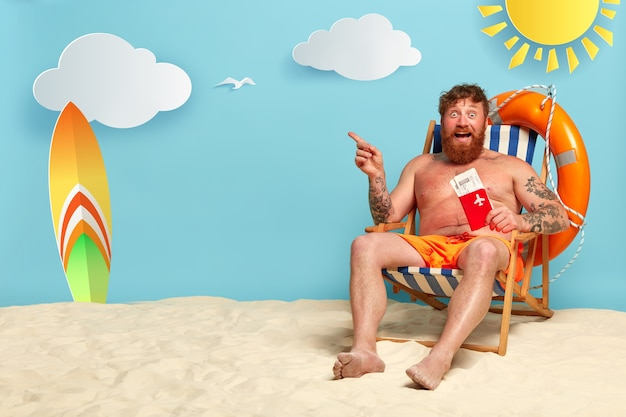 Топлесс бородатый рыжий мужчина позирует на пляже