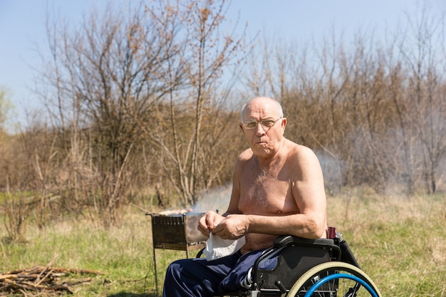 Topless handicap senior man, camping at the park, sitting on his wheelchair and preparing something while looking at the camera.