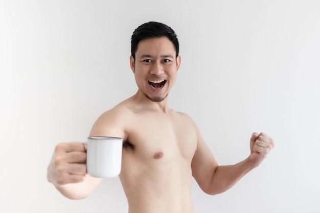 トップレスの健康なアジア人男性が健康的なコーヒーを飲みます。