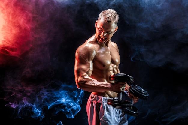 Топлесс мужчина, тренирующий бицепс с гантелями, позирует в студии, полной