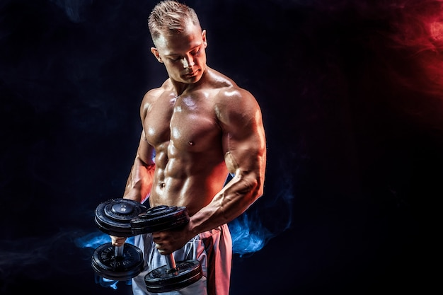 Topless man exercising biceps with dumbbells in