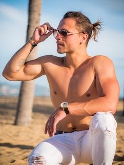 Топлесс человек в белых штанах на пляже