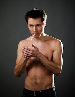 Topless man poses on dark gray background, holding cigarette in his mouth and lighter in his hands