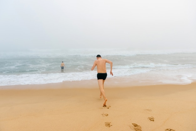 Topless man running from sandy beach in misty stormy ocean.