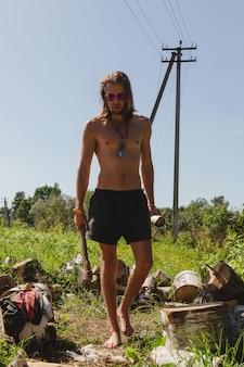 Топлесс сексуальный мужчина в шортах идет с дровоколом в одной руке и бревном в другой, окруженный деревянным шнуром.