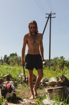 Topless sexy man in shorts is walking with a wood chopper in one hand and a log in another one surrounded by cord of wood.