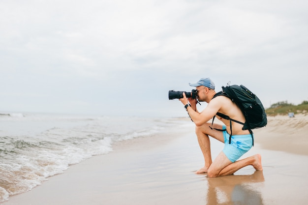 Topless traveler with photo camera taking picture of sea.