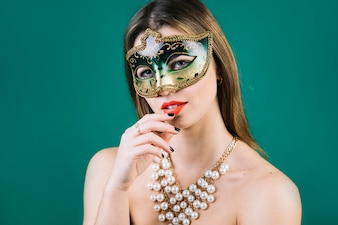 Topless woman wearing masquerade carnival mask and necklace on green backdrop