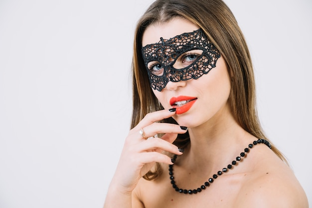 Topless woman wearing masquerade carnival mask and beads necklace