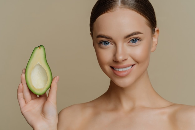 Topless young caucasian female model has dark combed hair smiles gently holds half of avocado