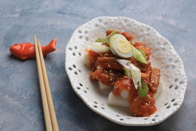 떡볶이 또는 떡볶이는 참깨를 곁들인 매운 소스 위에 야채와 어묵을 볶은 떡, 유명하고 인기있는 한국 길거리 음식입니다.
