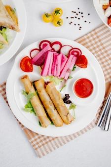 Topview di involtini primavera fritti con salsa e verdure sul tavolo