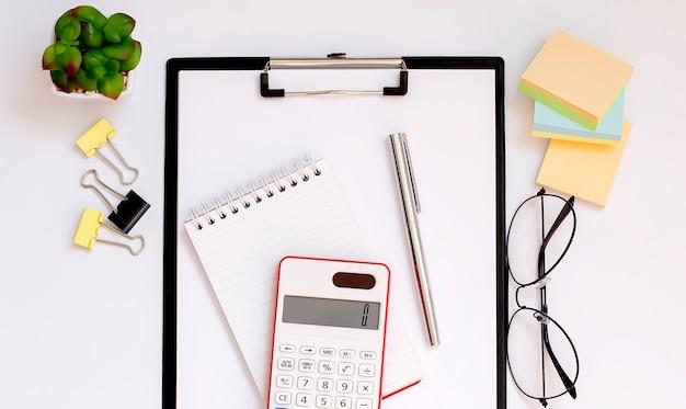 Вид сверху на белый рабочий стол с аккуратно организованными офисными инструментами и электронными гаджетами