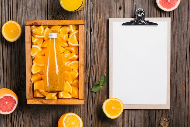 Topview orange juice and clipboard on wooden background