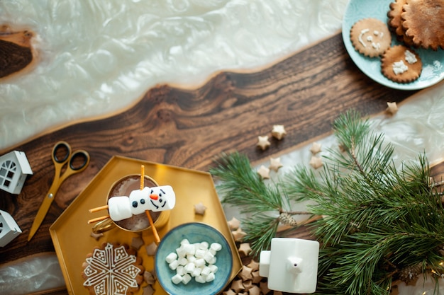 Topview table with christmas decor. snowmen from marshmallows decorated with sugar glaze. gingerbread cookies in the form of snowflakes.