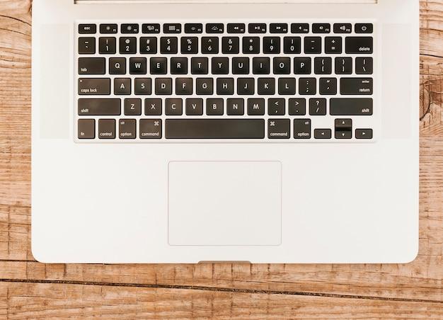 Topviewノートパソコンのキーボードの木製の背景