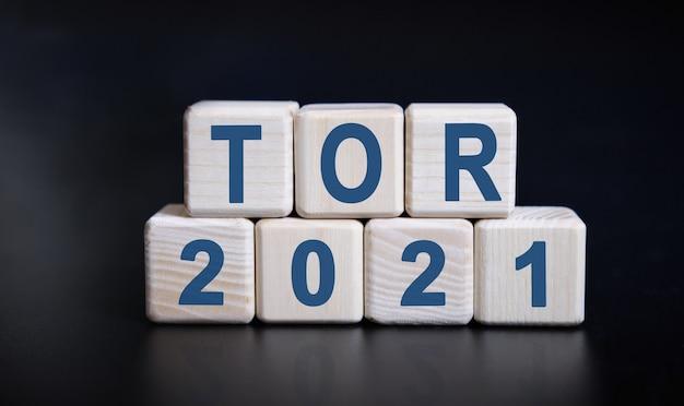 반사와 검은 배경에 나무 큐브에 토르 2021 텍스트.