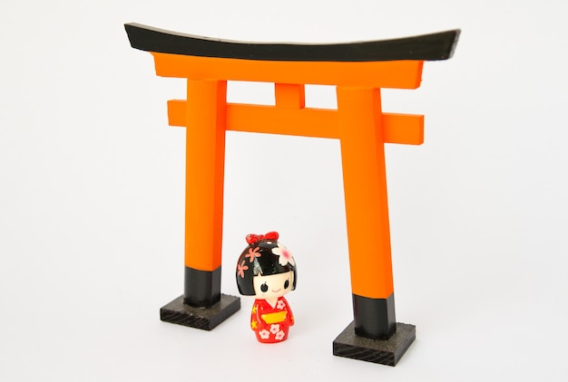 Torii gate with japanese dolls on white background