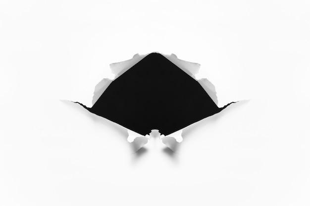 Разорванная черная дыра в листе белой бумаги.