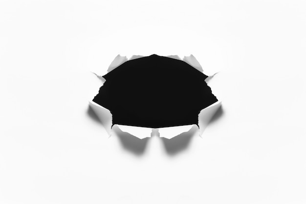 Torn black hole in the sheet of white paper.