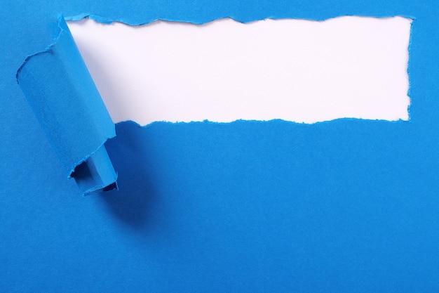 Torn blue paper strip curled edge background frame