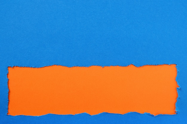 Torn blue paper strip orange background border frame