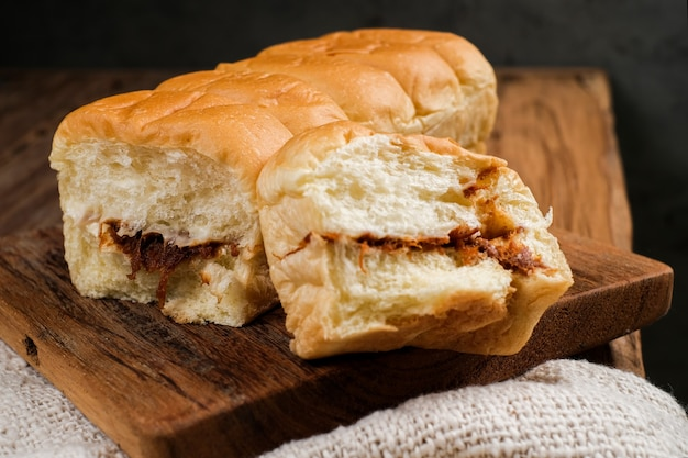 Torn bread filled with beef floss and mayonnaise on a wooden table