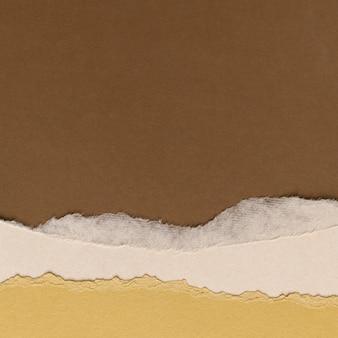 Bordo di carta marrone strappato su sfondo tono terra fatto a mano