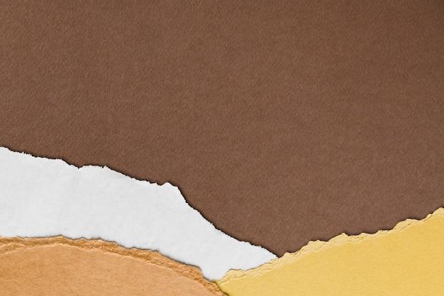 手作りのアーストーンの背景に破れた茶色の紙の境界線