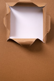 Torn brown paper square hole background vertical frame