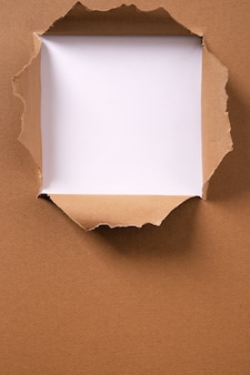 Torn brown paper square hole vertical background frame
