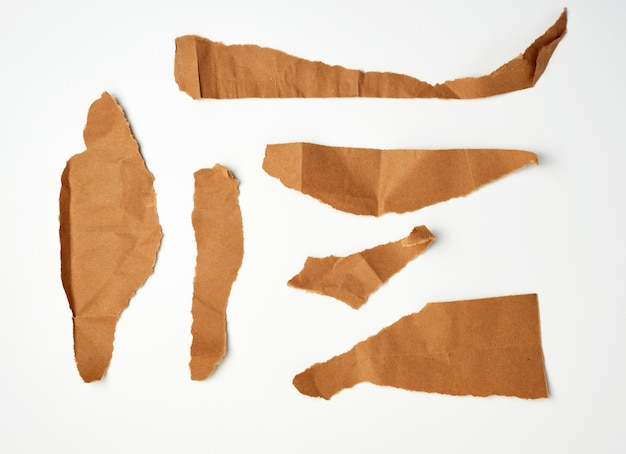 Torn brown pieces of parchment paper on a white