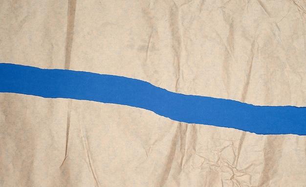 Разорванный коричневый лист бумаги на синем фоне, полный кадр