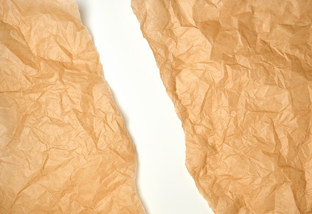 Torn crumpled brown parchment paper, white background