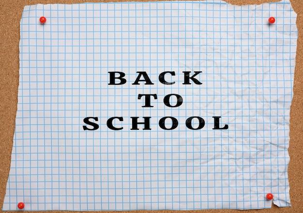 Рваный скомканный белый лист бумаги в клетке, приколотый к коричневой пробковой доске, с надписью «назад в школу»