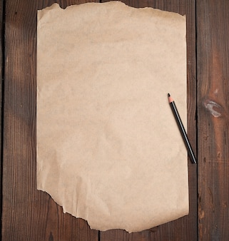 Torn empty sheet of brown paper and a black pencil on a wooden surface