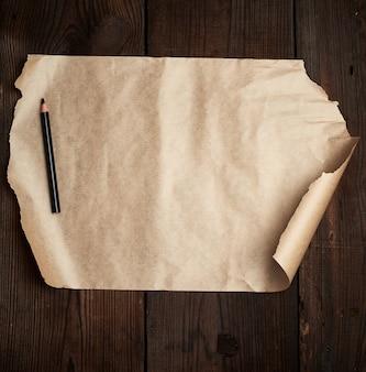 Разорванный пустой лист коричневой бумаги и черный карандаш на деревянной поверхности из старых досок