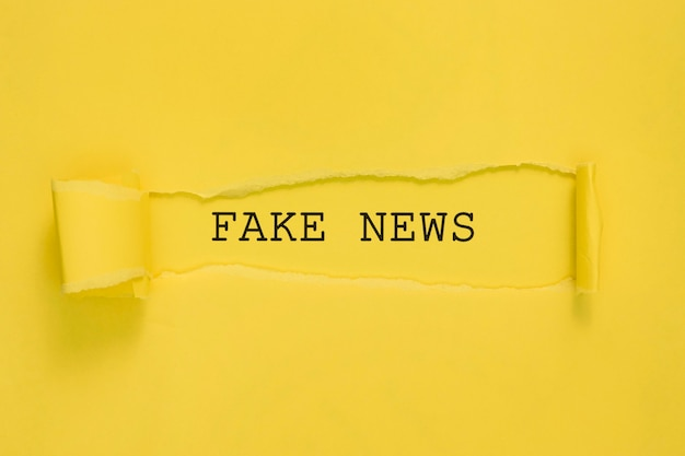 Torn fake news paper on yellow wall