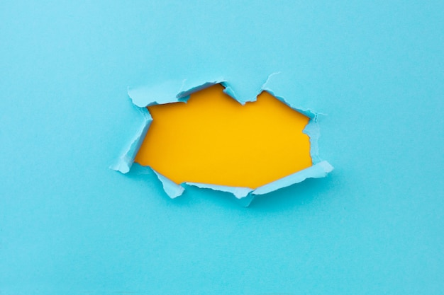 Torn hole in blue color and ripped of paper with yellow background. torn paper texture with copy space area for text
