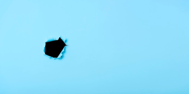 Torn hole in blue paper background.