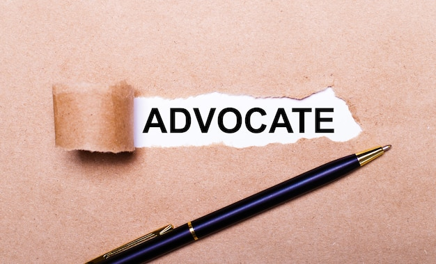 Torn kraft paper, white background with the text advocate. nearby is a black handle. view from above