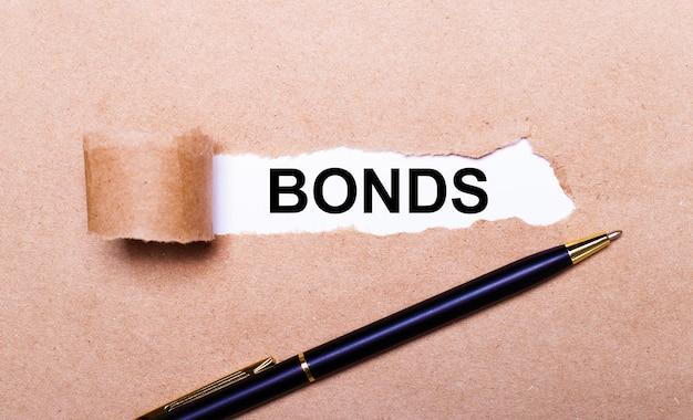 Рваная крафт-бумага, белый фон с текстом облигации. рядом черная ручка. вид сверху