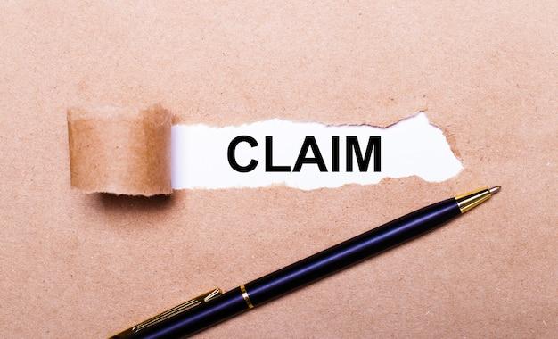Рваная крафт-бумага, белый фон с текстом претензия. рядом черная ручка. вид сверху Premium Фотографии