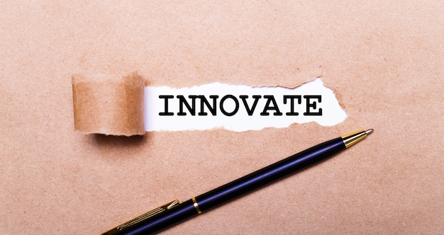 Рваная крафт-бумага, белый фон с надписью innovate. рядом черная ручка. вид сверху