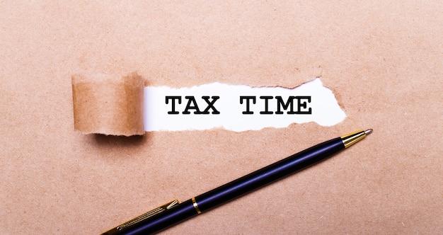 Рваная крафт-бумага, белый фон с текстом налоговое время. рядом черная ручка. вид сверху
