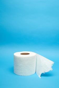 Оторванный белый рулон туалетной бумаги на минималистичном синем фоне