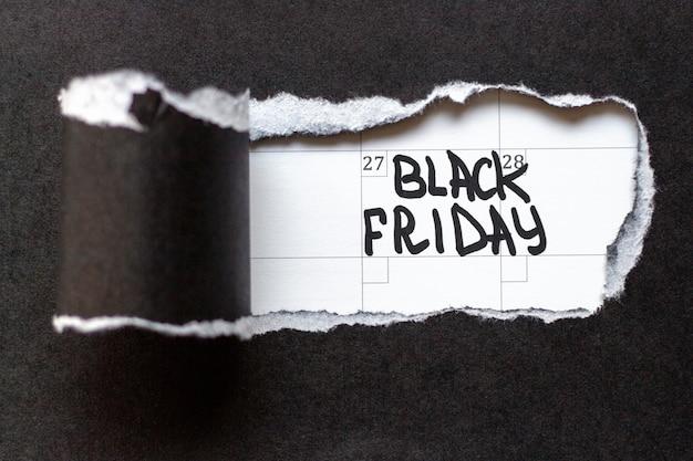 Рваная бумага и надпись черная пятница на белой полосе